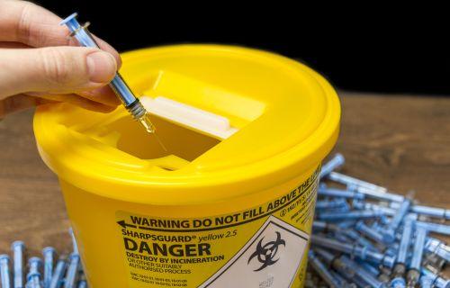 Needles being put into a sharps bin