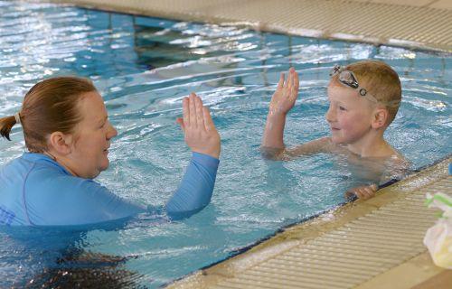 Swim teacher high fives student in pool